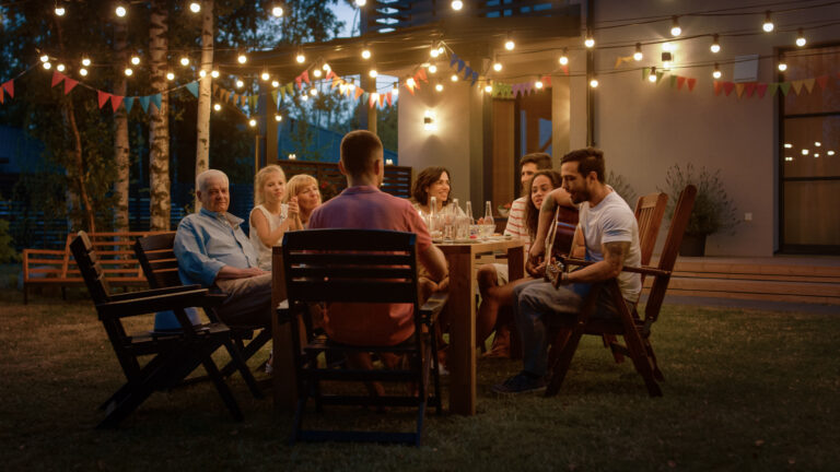 Family entertaining at a backyard table, summer evening with string lighting, beautiful backyard landscaping