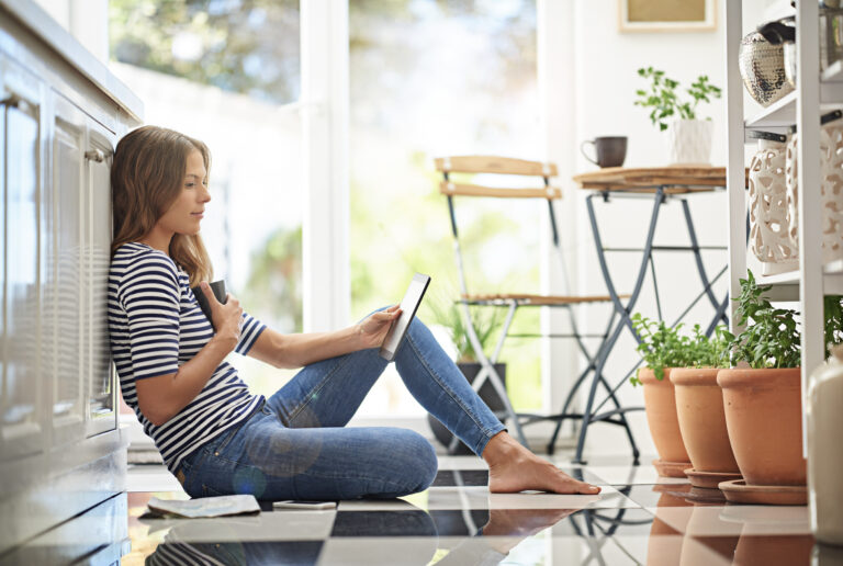 Woman sitting on floor looking at tablet