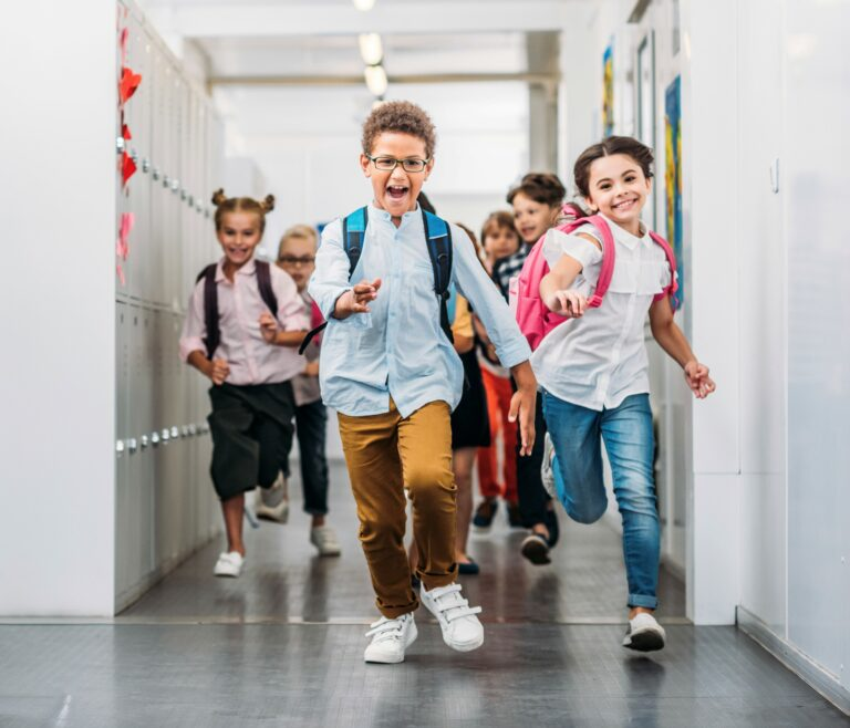 Young children wearing backpacks running excitedly through the hallway at school, lockers line the walls