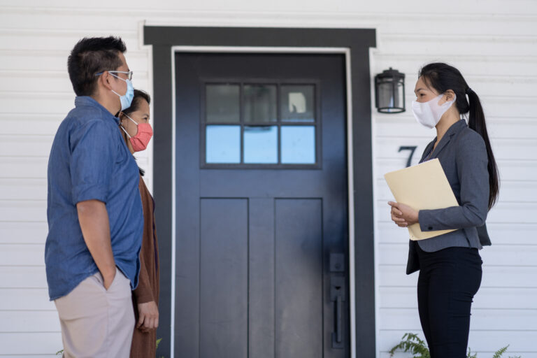 Female realtor standing socially distanced from middle-aged couple clients outside a house, all wearing masks