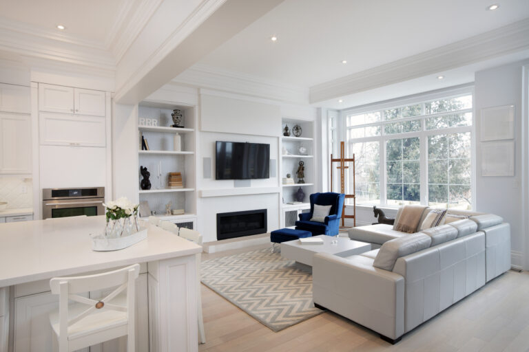 Modern, clean living room and kitchen with white couches, navy blue accent chair, white cabinets, television mounted on the wall