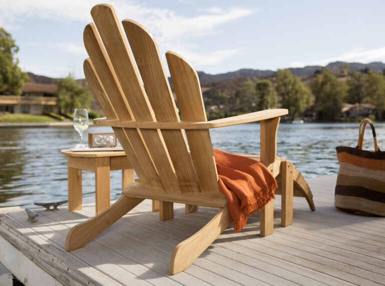 Natural wood muskoka chair on dock draped with orange blanket, small table beside chair with wine glass and portable speaker