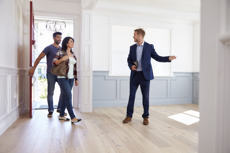 Realtor in a blue suit shows a young couple a property, couple entering through front door