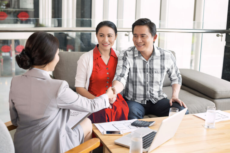 Asian couple, woman in red dress, sitting on a couch, smiling and shaking hands with a realtor