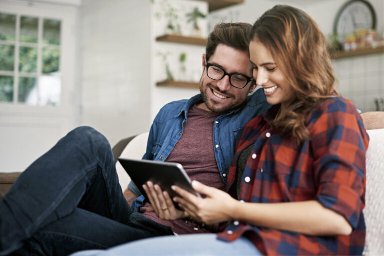 Young couple smiling, sitting on the couch reading blog post on a tablet, man in blue shirt, woman in plaid shirt