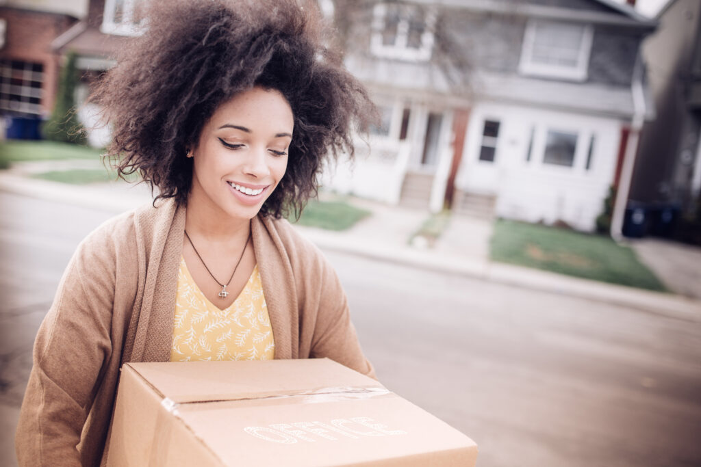 Happy, young woman carrying a moving box to her new home