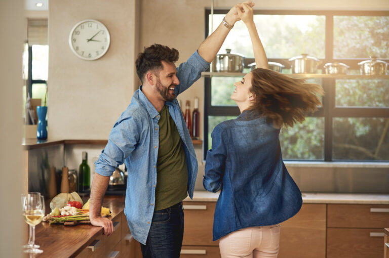 Young, happy couple dancing in the kitchen; warm sunlight pouring in through the window