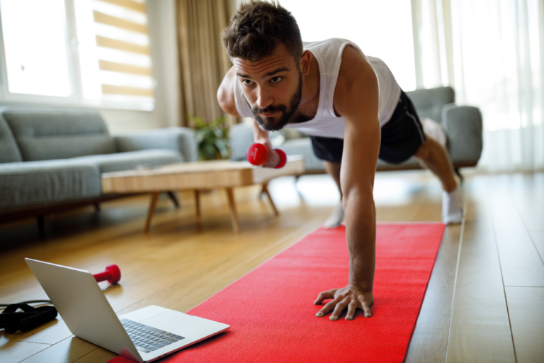 Athletic man in white tank, black shorts holding one-arm plank on a yoga mat in his living room; weighted row with other arm