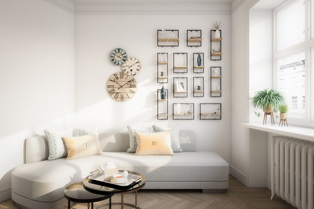Bright room with neutral tones, sectional couch, round nesting coffee tables, plants on the window sill