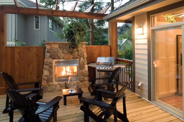Outdoor patio with fireplace, muskoka chairs and barbeque grill