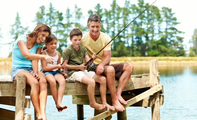 Mother and father sitting on a dock with their daughter and son who are fishing, smiling