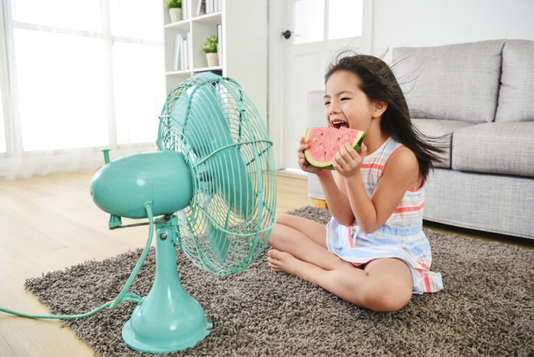 Young girl gleefully eating watermelon, seated in front of a blue fan, cooling herself on a hot summer day