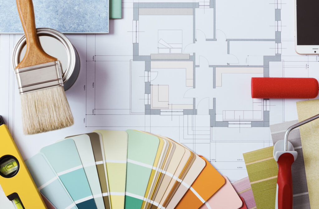 Floor plans, small paint can and brush, level, colourful paint chips and red roller
