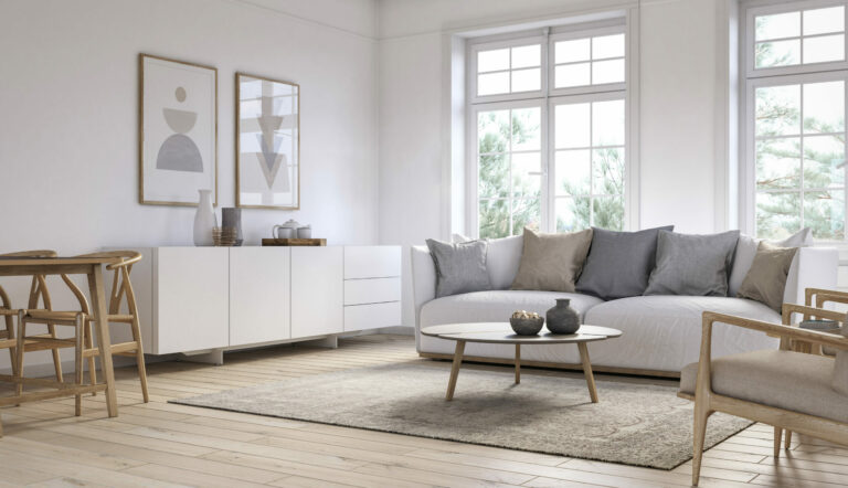 large, clean room with grey couch, round wooden coffee table and large windows
