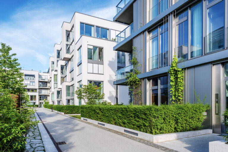 Exterior of low rise condominium buildings with landscaped walkway