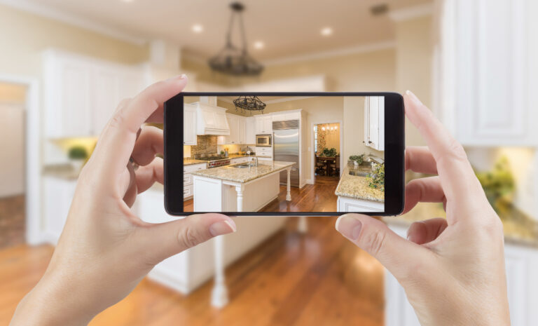 Hands taking a photo of renovated kitchen on a cell phone