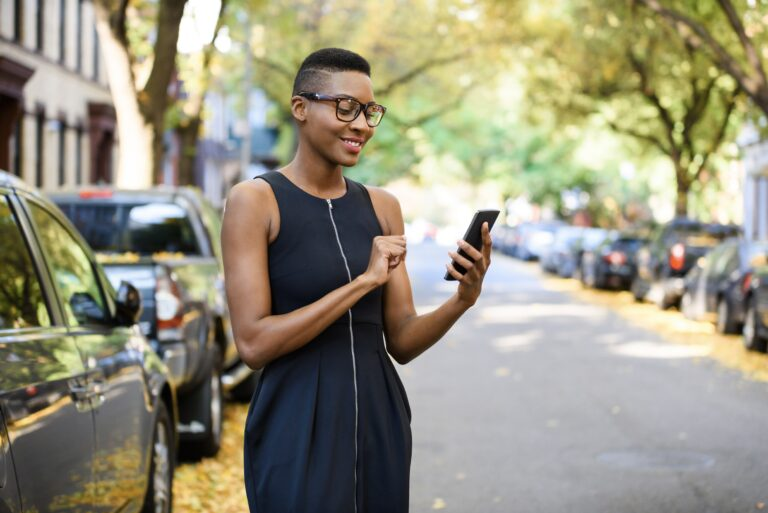 Young woman in the city using her cell phone to search for a property