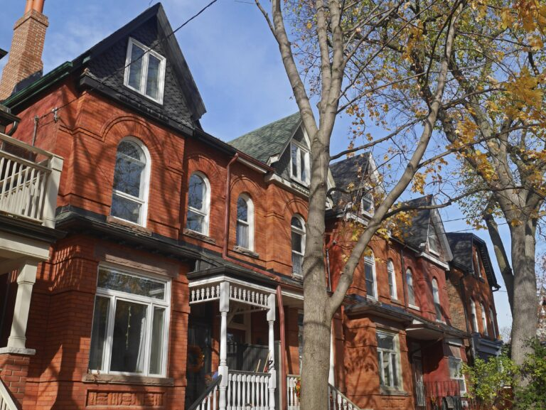 Red brick Victorian row homes with large tree in front, sunny day