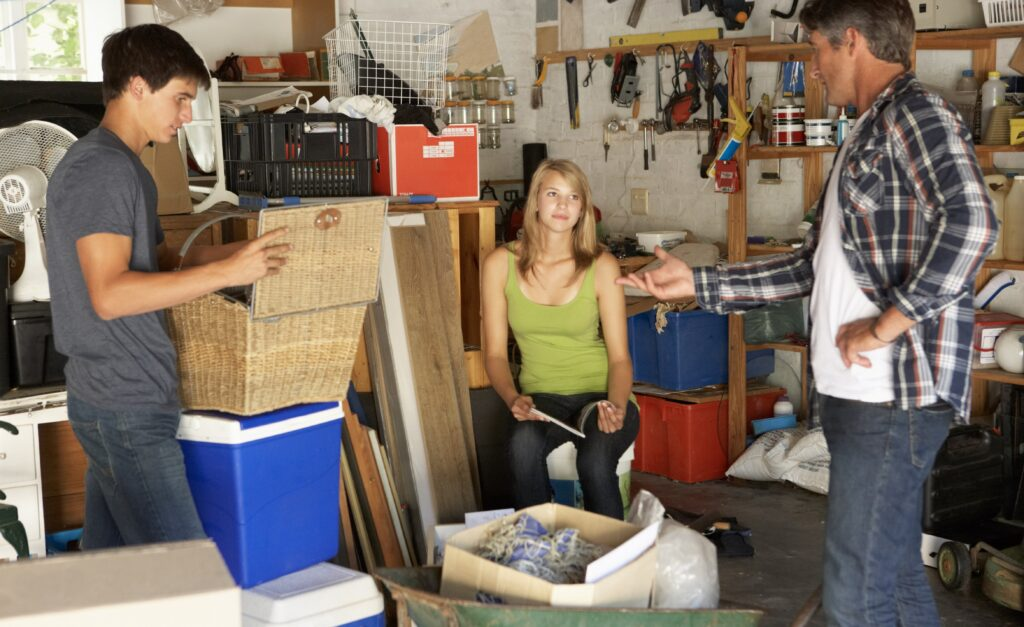 Dad with teenage daughter and son organizing boxes in the garage