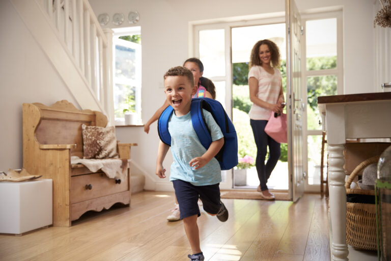 Young boy and his older sister excitedly running through the door after school