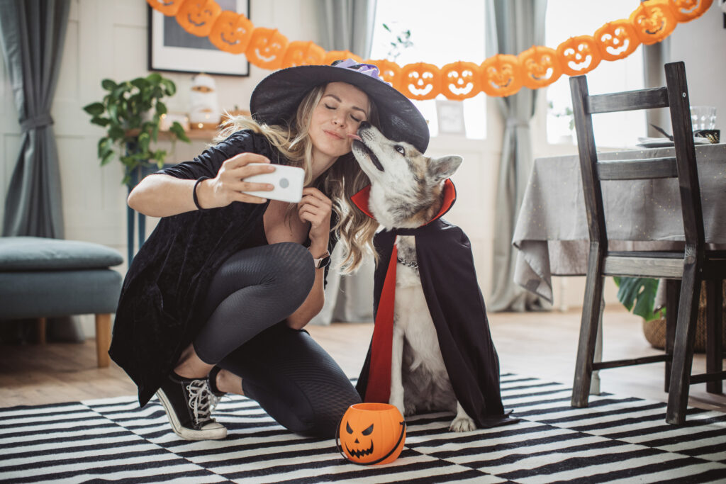 Woman and dog dressed in Halloween costumes taking a selfie photo