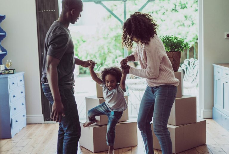Parents playing with young child in their living room, with moving boxes and large window to yard in the background