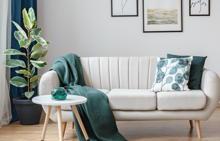 Modern living room with ivory couch and teal accent pillows and blanket